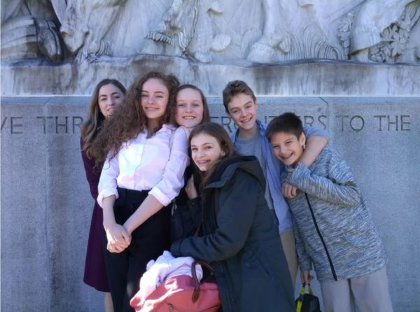 A group of eighth graders pose in front of a statue in Seattle